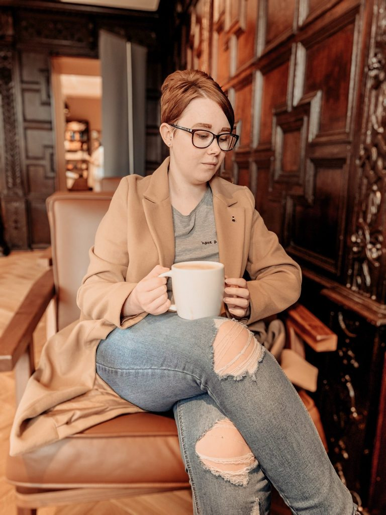 A picture of Jade Marie looking off to one side in Starbucks, with a caramel latte resting on her legs