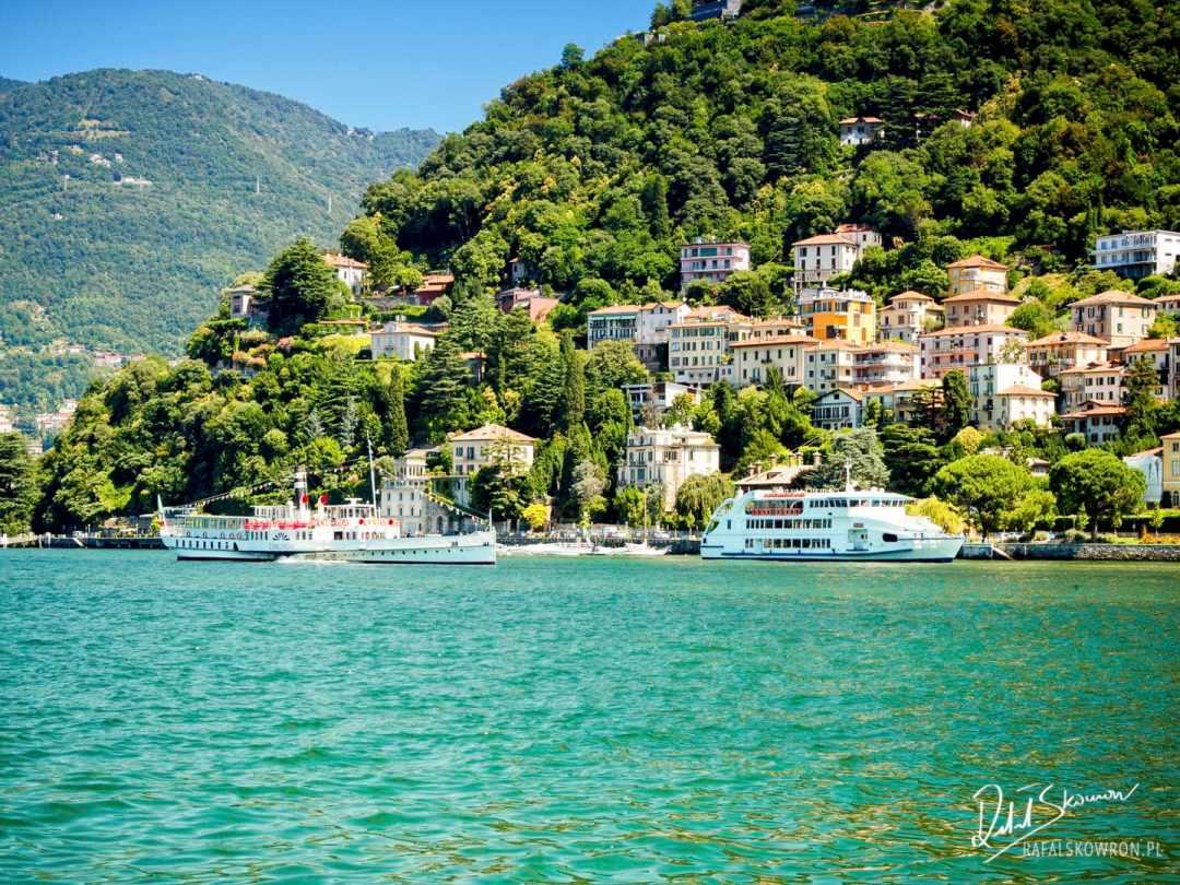 Widok na jezioro Como z miasta Como. Na zdjęciu widać jezioro, na nim statki wycieczkowe i wzgórze z zabudowaniami.