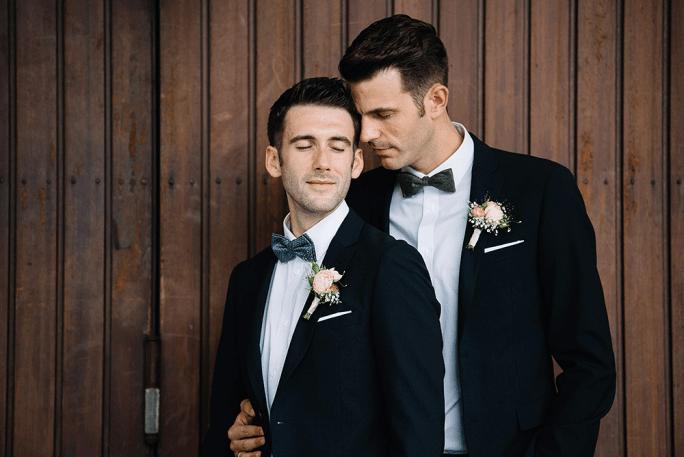 Unsere Hochzeitsfotos: Jeroen & Florian mit holzem Hintergrund - Gay Wedding