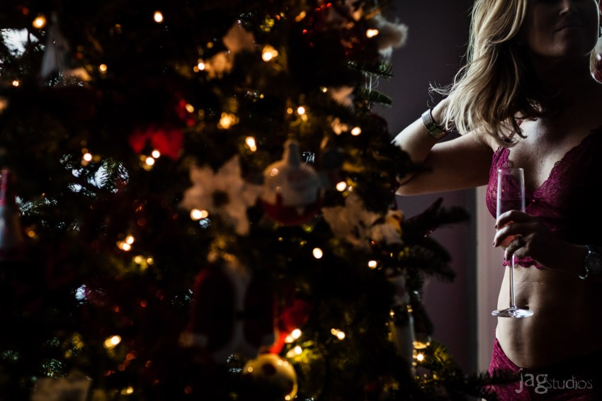 beautiful woman is red lingerie with champagne glass and Christmas tree JAGstudios photography A Christmas Boudoir Photography Session