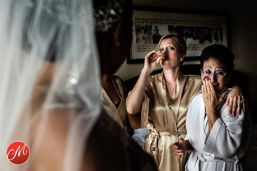 sister of bride drinking a shot with mom crying looking at bride