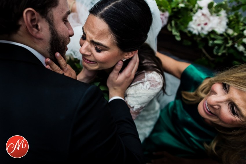 bride crying as groom kisses her and mom looks on