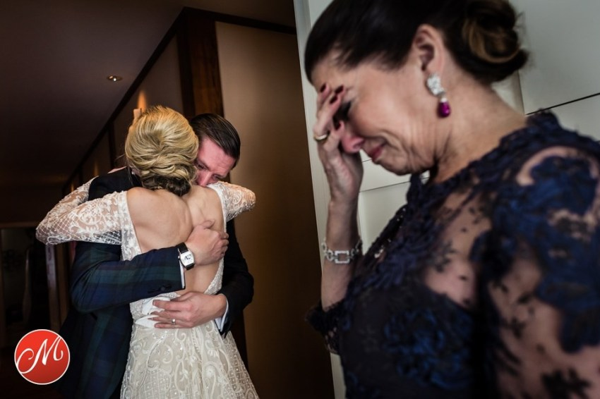 brother hugs bride as mom cries
