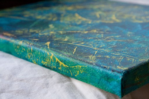 side of canvas and details of abstract leaves painting. Turquoise background with yellow leaves.