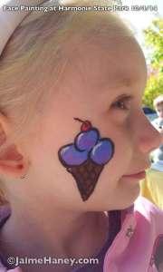 Purple ice cream cone face painting on cheek