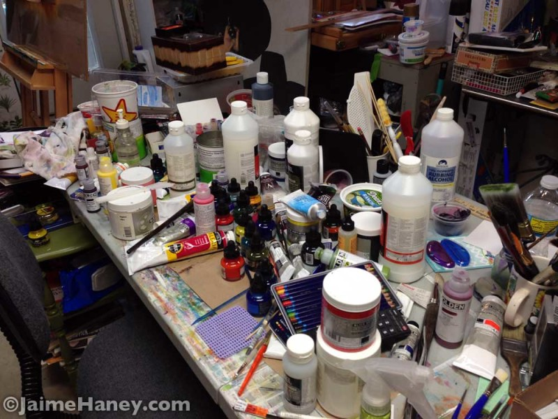 messy work table of artist in the art studio