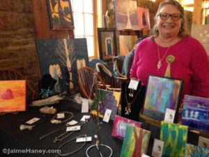 Nancy Pace with her jewelry and paintings