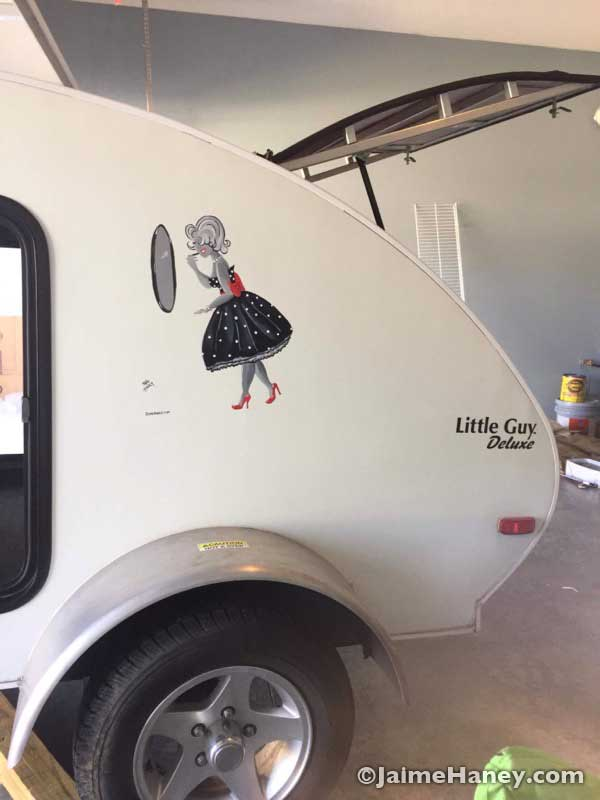 A 1950's Glamour Girl painted on the side of a Little Guy Travel Trailer