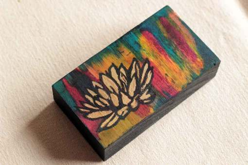 Golden lotus art block painted against a richly toned background on a small piece of wood.