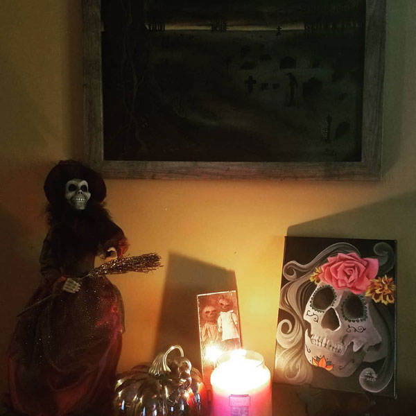 A spooky vignette with a witch, pumpkin, lit candle and sugar skull painting.