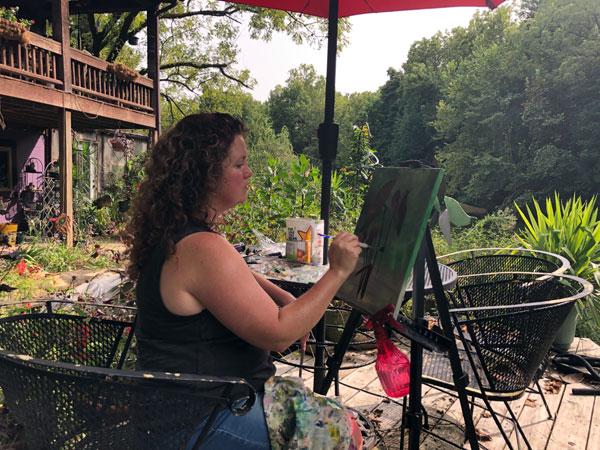 Jaime Haney painting outside at Studio Gardens