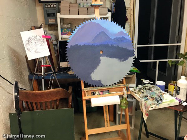blocking in the mountains and foreground of the landscape scene for a custom painted saw blade
