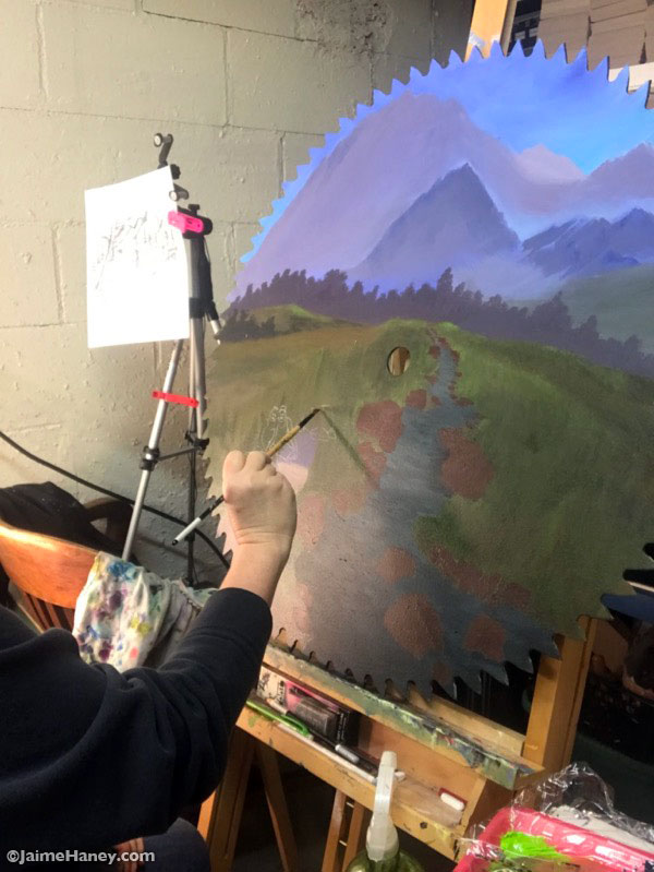 Indiana artist Jaime Haney painting a landscape on a saw blade.