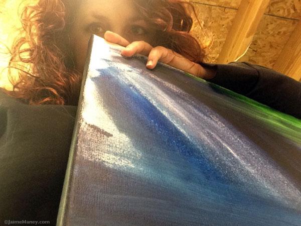 artist peering over canvas