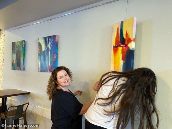 Autumn helping Jaime hang her paintings