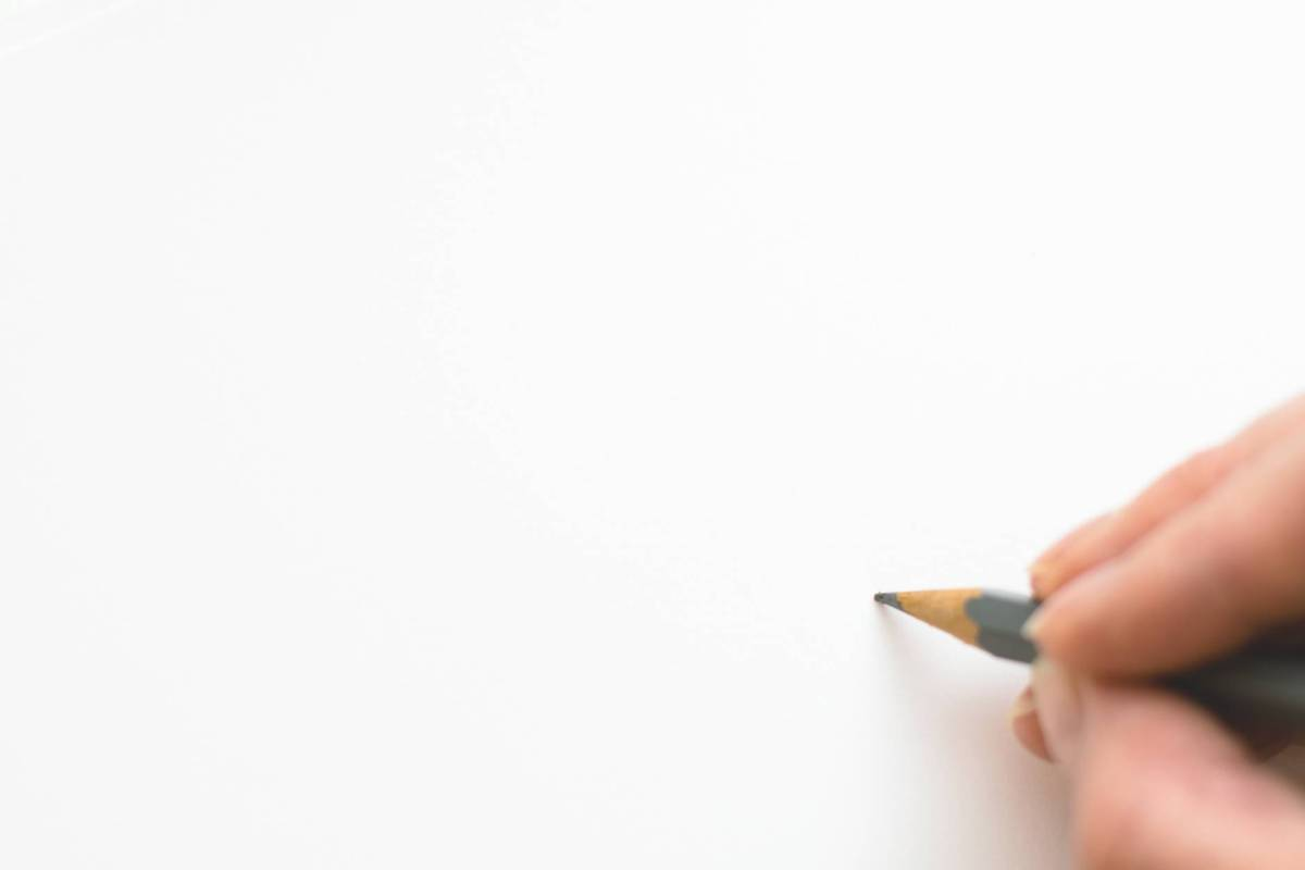 close up of hand holding pencil over white background