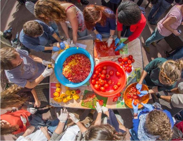 Une dizaine de personnes cuisine autour d'une table, dehors. La table est recouverte de saladiers avec des fruits de saison.