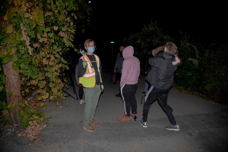A group of people walking down a path at night  Description automatically generated with medium confidence