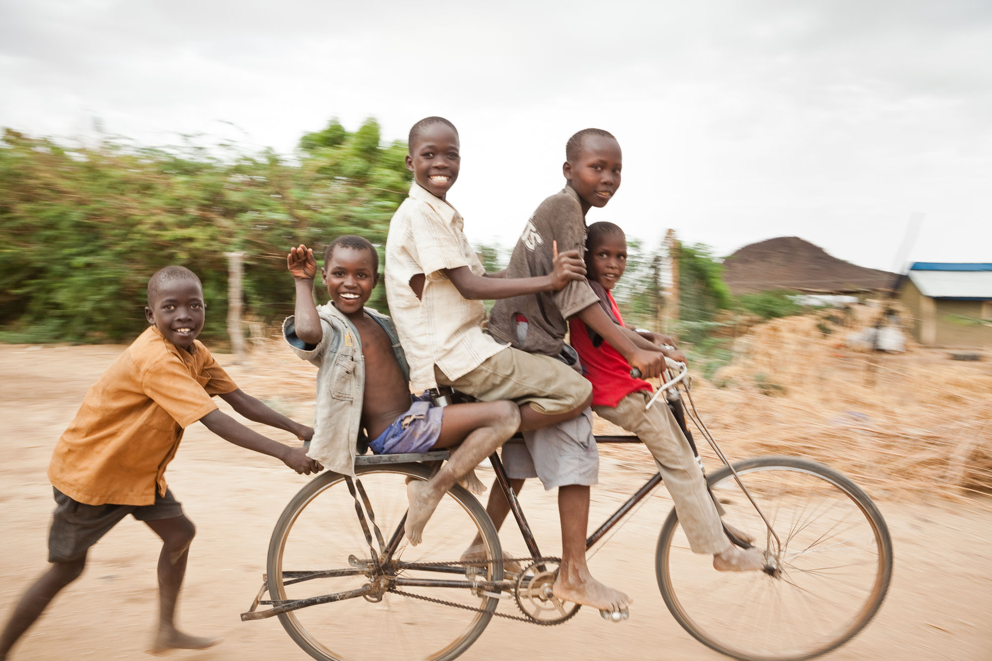 Children play together on a bicycle in Lodwar, Kenya.