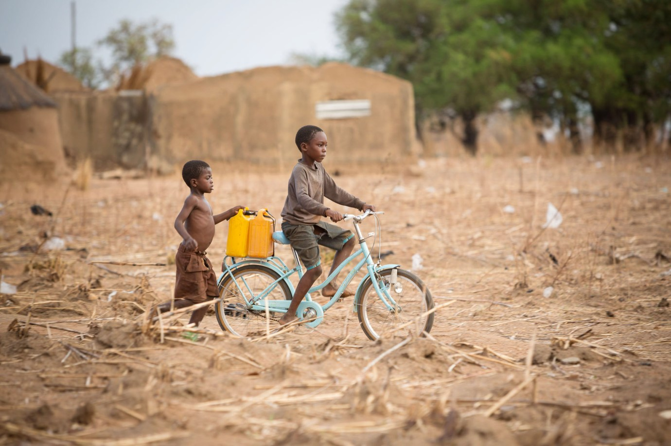 Children fetch water with a bicycle in Talensi District, Ghana.