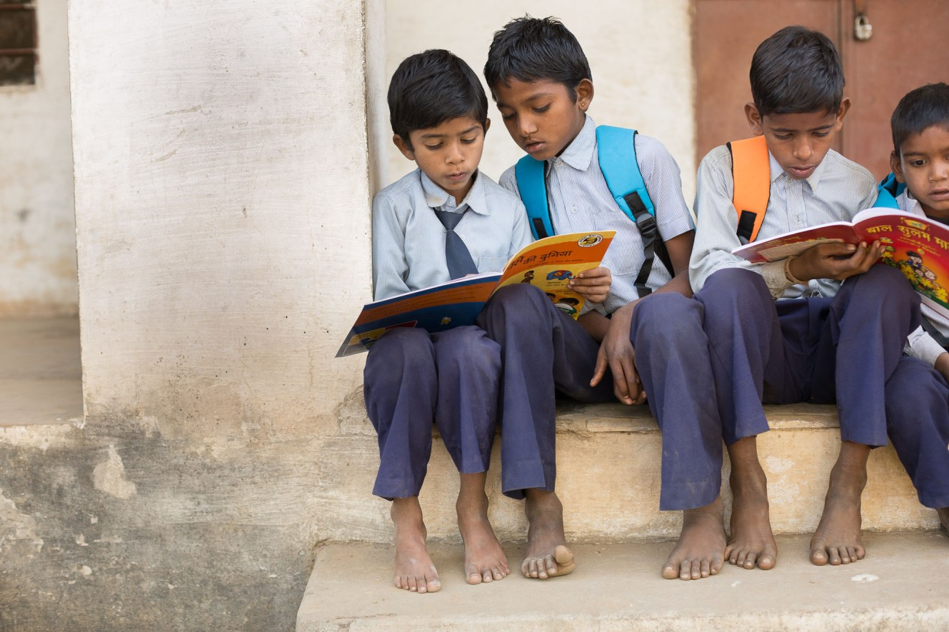 Children read together outside their school in Udaipur District, India.