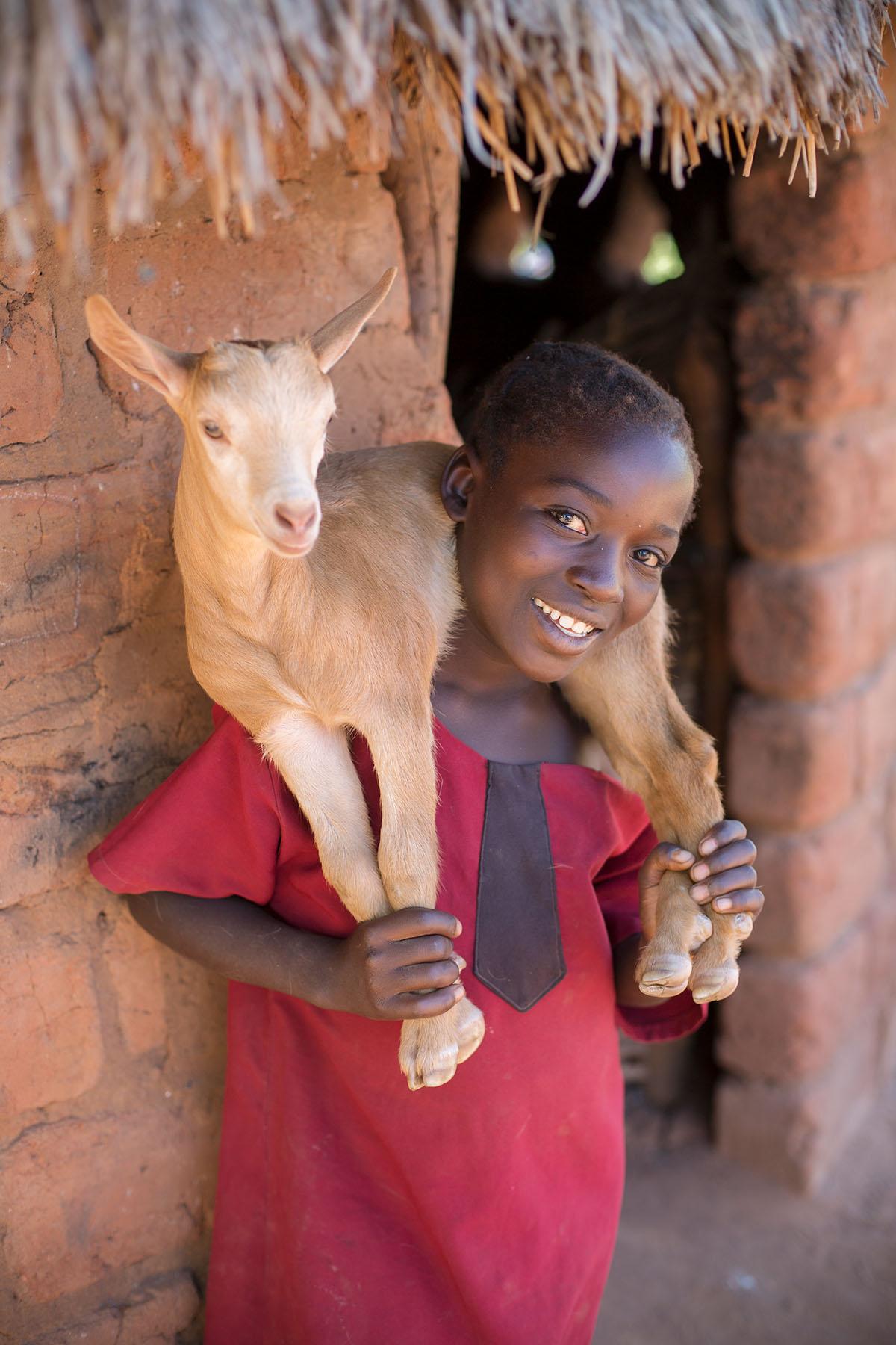 Royce (11) holds a goat in Luangwa, Zambia.