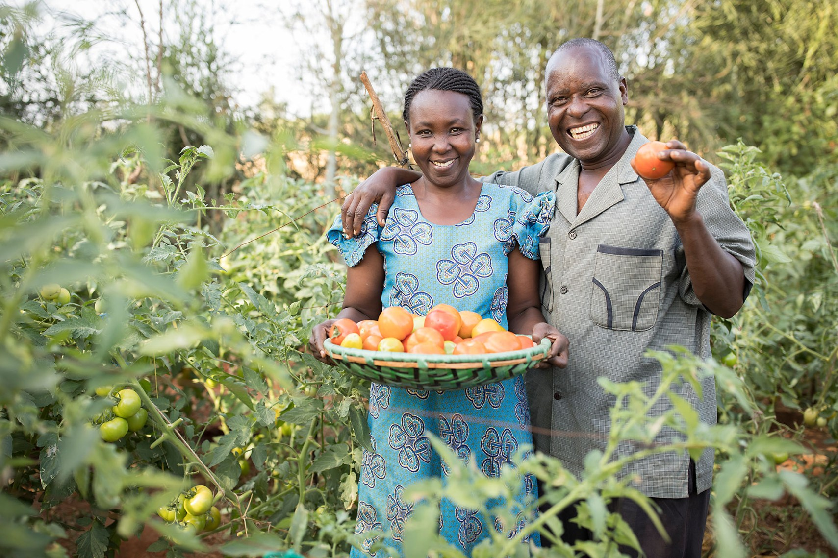 Agnes Nduku (46) and her husband Alfonse Nzuki (53) hold freshly harvested tomatoes on their family's small farm in Makueni County, Kenya.