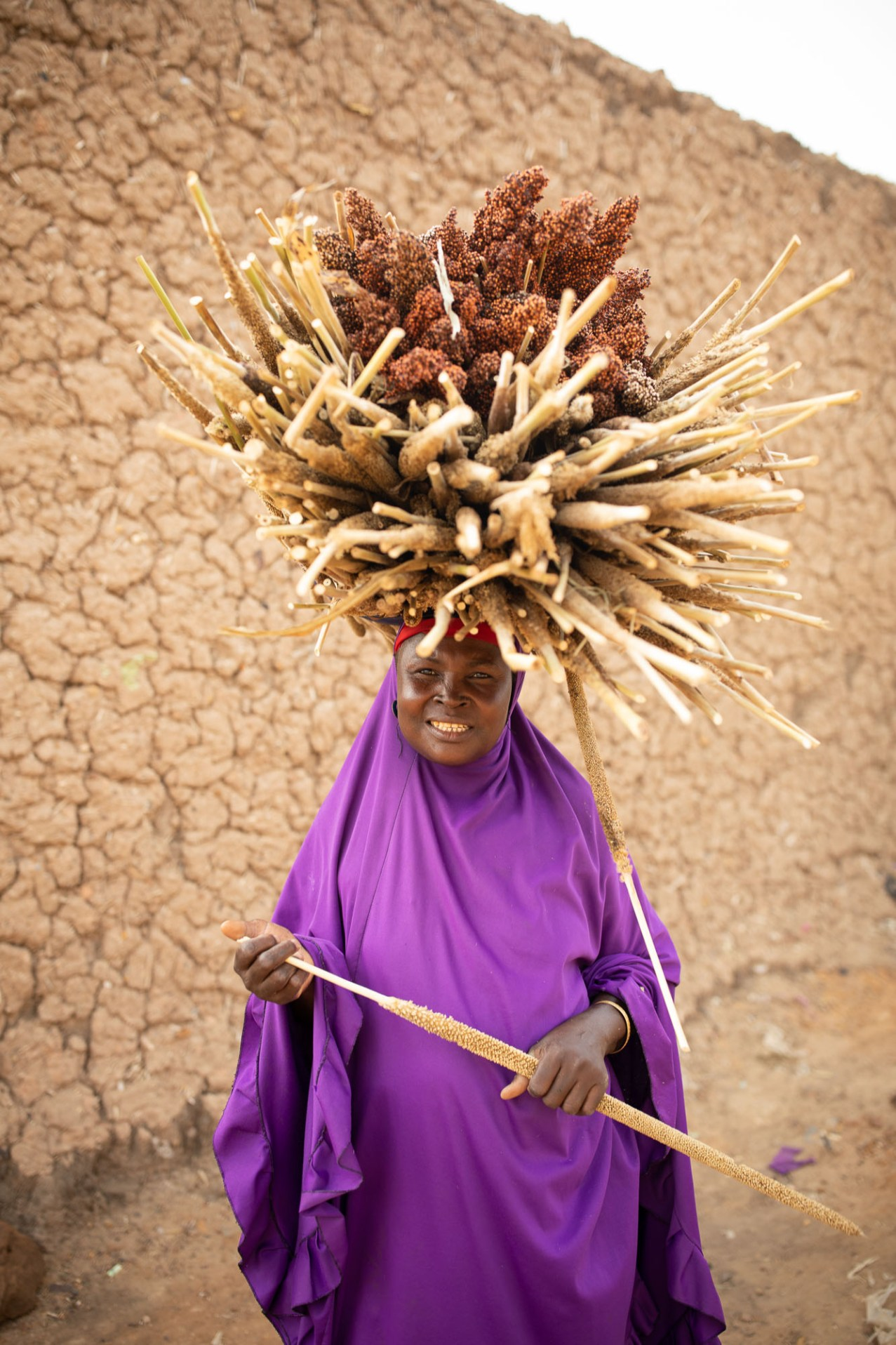 Emma Ali (45) carries a millet and sorghum harvest home from the farm in Tahoua Region, Niger.
