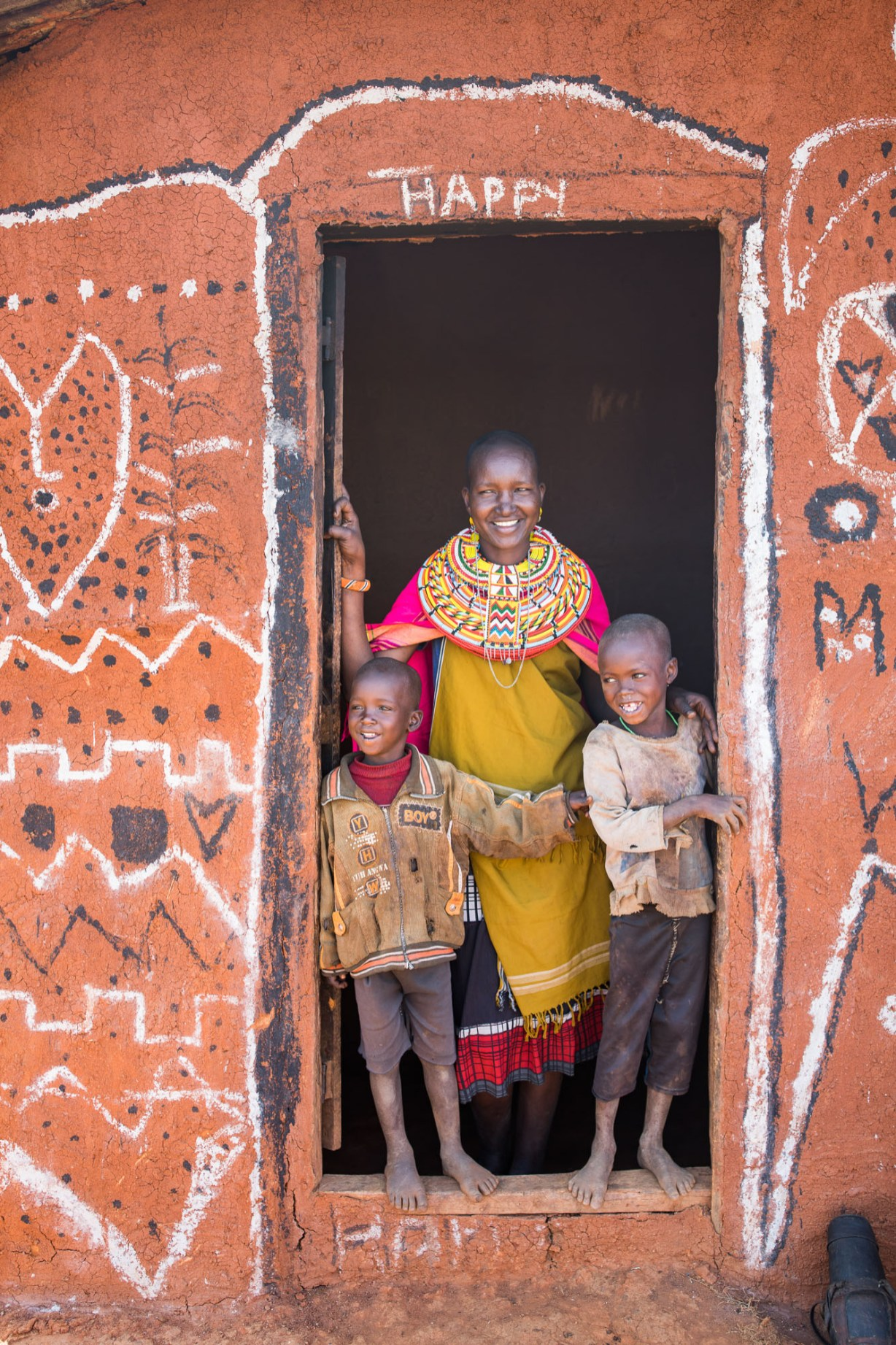 A family stands in the doorway of their home in Samburu County, Kenya.