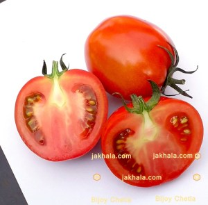 There are two halves of a tomato beside a tomato.