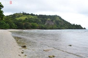 Pantai di Utara, tenang dengan bukit latar belakang bukit hijau..