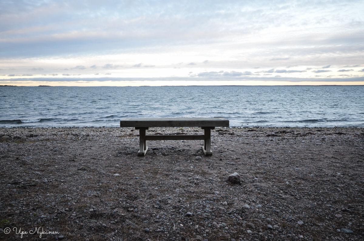 Yksinäinen penkki meren rannassa Tulliniemen luontopolulla