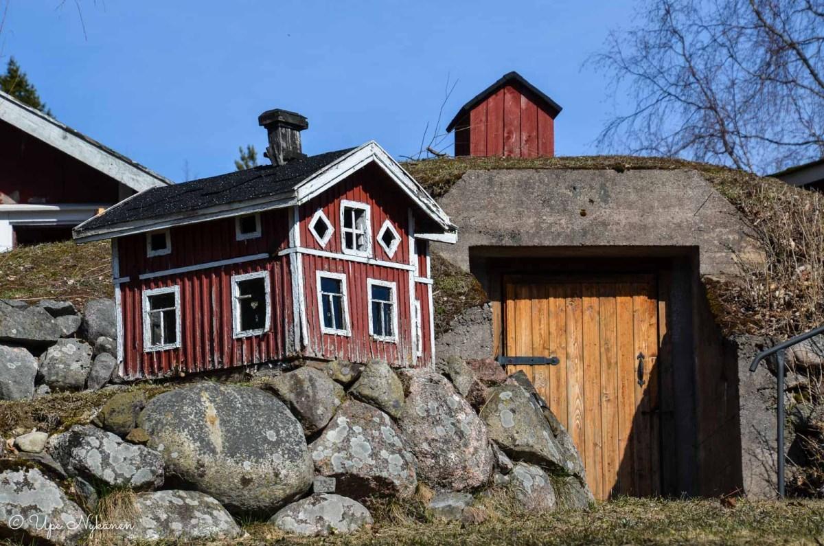 Pieni punainen miniatyyrimökki talon pihassa.