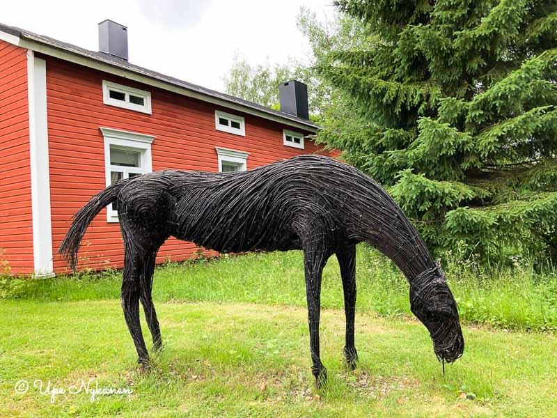 Pajun- tai koivunoksista muotoiltu hevosveistos, hevonen asennossa jossa syö ruohoa.
