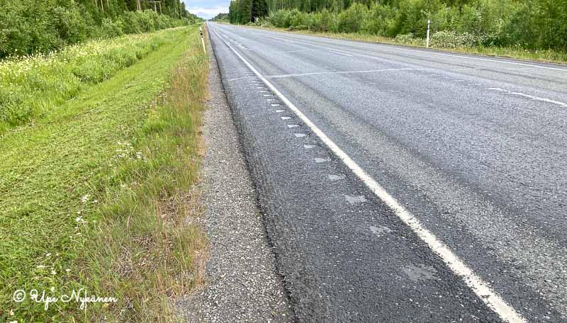 Piikkisuora nelostie ja sen piennar, jossa leveähkö asvalttiosa, sen vasemmalla puolella sorapintaa ja tienvarren leikattu nurmi.