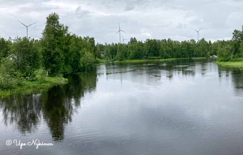 Tyyni Olhavanjoki, jonka takana näkyy neljä tuulivoimalaa.