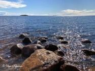 Sininen taivas ja pilviä, Perämeren rantakiviä ja auringossa välkehtivä sininen Perämeri. Paikka: Merihelmi.