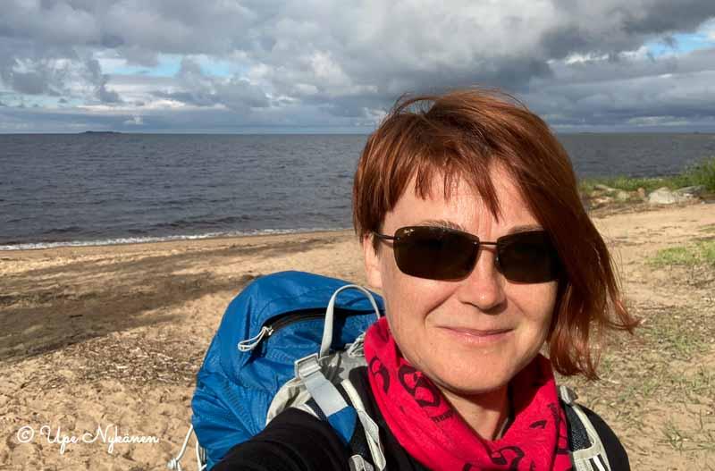 Upe aurinkolasit päässä ja reppu selässä Perämeren hiekkarannalla, pilviä taivaalla.