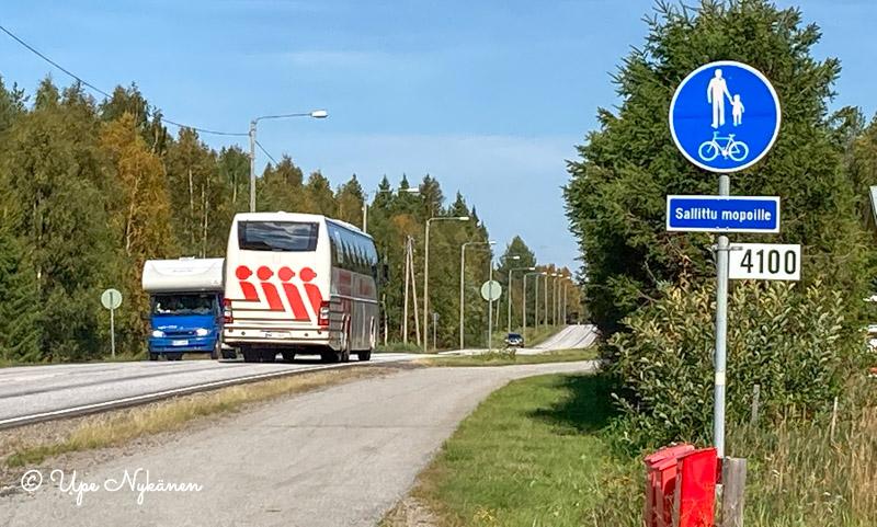 Kevyen liikenteen väylä, sen vieressä nelostie, V. Alamäen linja-auto ajaa kohti Rovaniemeä.