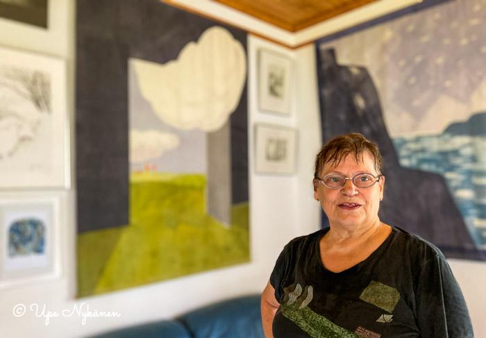 Taiteilija Liisa Halonen-Laiti, takana hänen taulujaan.