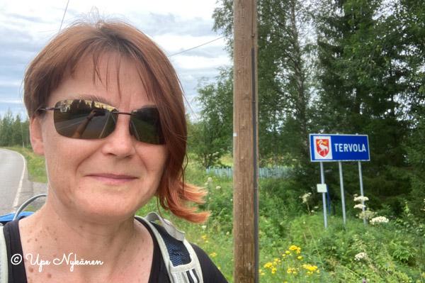 Upe aurinkolasit päässä, taustalla Tervolan kunnan rajan kyltti.