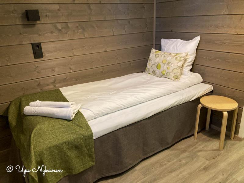 Yhden hengen sänky, valkoiset petivaatteet, sängyn vieressä yöpöytänä jakkara, harmaat lautaseinät ja parkettilattia.