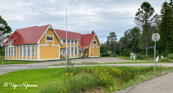 Liedakkalan puinen koulurakennus, punainen peltikatto, keltaiset seinät ja valkoiset nurkkalaudat.