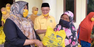 Cek Endra dan istri menyerahkan secara simbolis paket bahan pokok untuk warga.