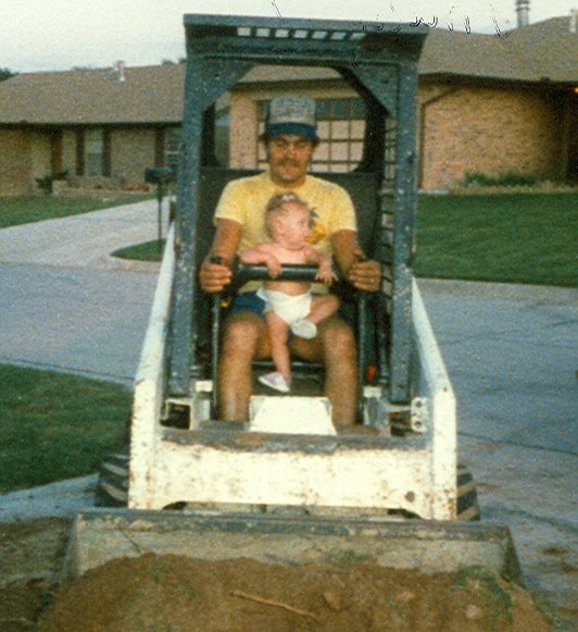 During high school and after Kay and I were married, I worked for my father in his swimming pool construction business. Emily was born in 1985, right before I started into computers. Here she is helping me drive my Dad's Bobcat skid steer loader.