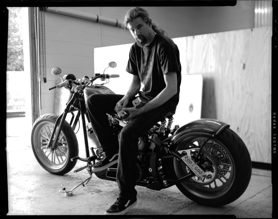 An authentic portrait of Bryan Nikkel on a hand built motorcycle he built while working at Brass Ball Bobbers motorcycle company.
