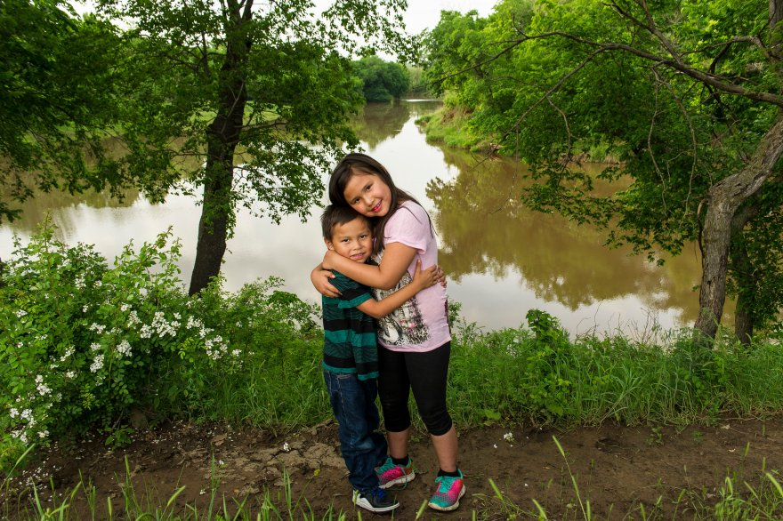Eddy Red Eagle's grandchildren pick flowers in front of Bird Creek, which is the boundary to his family land.
