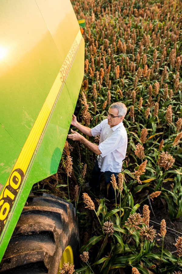 Oklahoma Secretary of Agriculture Jim Reese closes a maintenance panel on his John Deere combine.