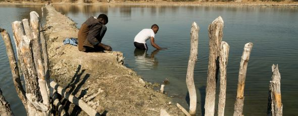 Grad student Karim Mtili (right) collects gas samples in Itumbula, Tanzania Bloomberg | James Alexander Michie