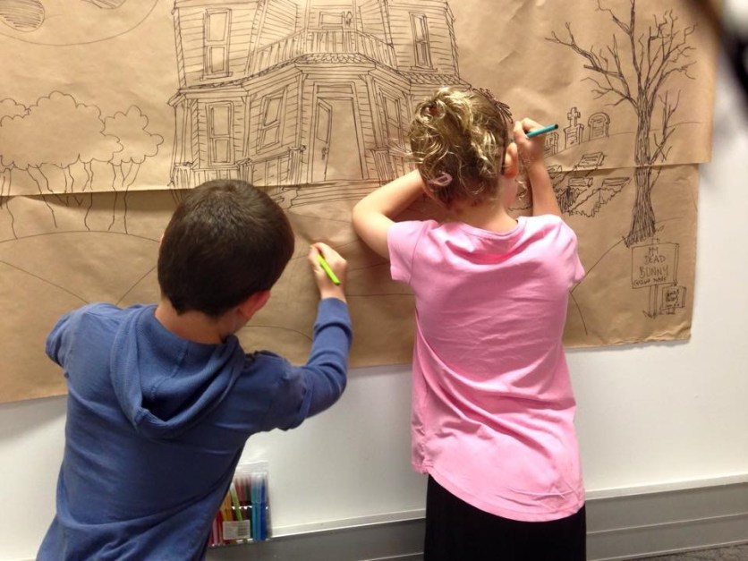 kids adding their designs to the zombie mural